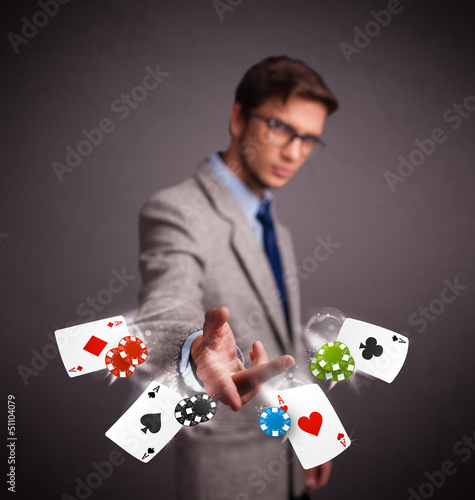 Young man playing with poker cards and chips