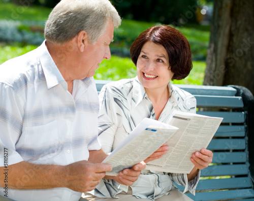 Happy senior couple reading outdoors