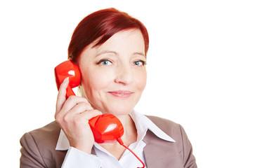 Glückliche Geschäftsfrau mit rotem Telefonhörer