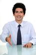 Businessman sat at desk offering to shake-hand