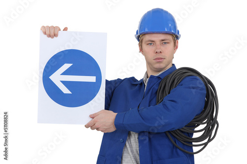 Electrician holding directional road sign
