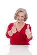 Großmutter drückt die Daumen - isoliert in Rot