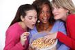 three friends eating popcorn