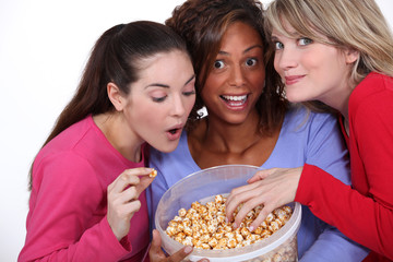 three friends eating popcorn