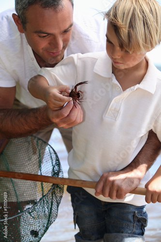 Father and son with a crab