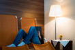 girl reads book lying in lounger with lamp front of wooden wall