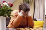 Behinderte Frau grübelt vor einem leeren Schachbrett