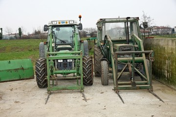two green tractors parked on a farm outdoors