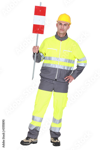 construction worker in safety outfit holding construction sign