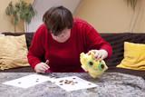 Behinderte Frau blickt verzweifelt auf wenig Geld