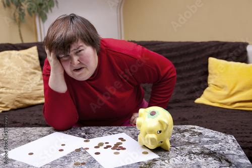 Behinderte Frau blickt verzweifelt, vor ihr Rechnungen