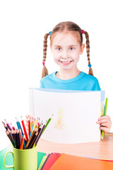 Cute llittle girl drawing in a sketchbook with colored pencils