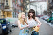 Two young beautiful women sightseeing and looking at the map in