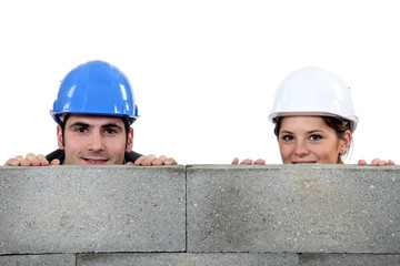 male bricklayer and female counterpart hiding behind wall
