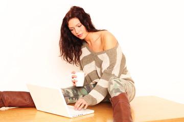 Frau sitzt auf dem Tisch mit Laptop