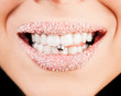 Smiling lips with sugar showing piercing