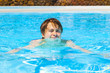 cute handsome teenage boy swims in the pool