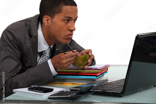 Man eating Chinese food at a laptop