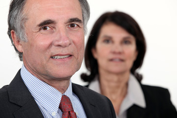 Older businessman with a woman in the background