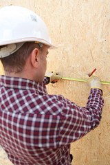Man using tape measure to mark wooden panel