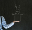 Man pulling rabbit from magic hat blackboard background