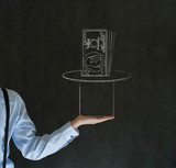 Man pulling money from magic hat blackboard background