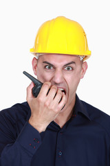 businessman wearing helmet and shouting on a walkie talkie