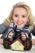 Frau schützt Haus mit Ohrwärmer vor Kälte