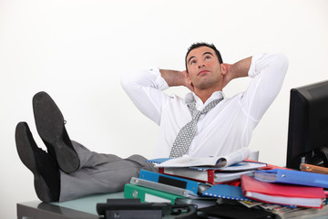 Businessman reclining in his chair despite being overworked