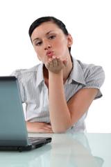 Woman at desk blowing kiss