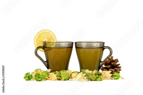 Two cups of green tea with lemon, fir-cone and physalis
