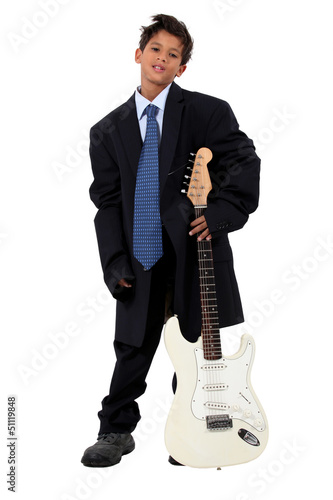 Boy in loose fitting suit stood with electric guitar