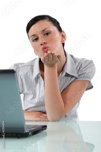 Woman at desk blowing kiss