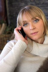 Blond woman making phone call whilst sat on cosy sofa
