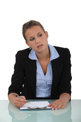 Blond woman sat at desk with blank clip-board