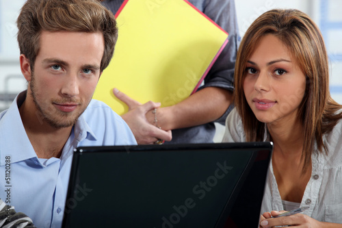 Interns sitting at a desk with computer