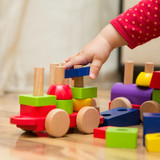 Baby's hand playing with wooden toys