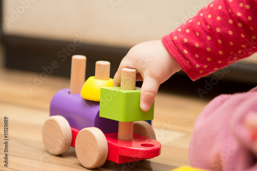 Baby's hand playing with wooden toy