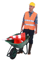 Man with wheelbarrow full of traffic cones