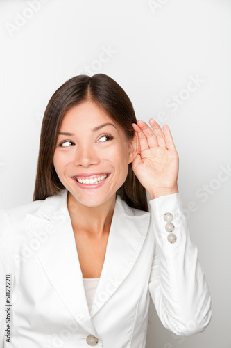 Business woman listening with hand to ear concept