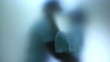 Couple kissing in bathroom. Soft effect from frosted glass.