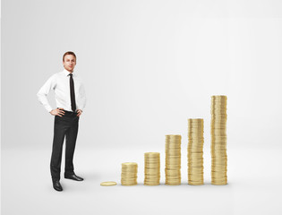 Businessman and increasing columns of gold coins