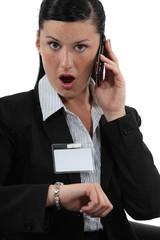 Shocked businesswoman talking on her cellphone