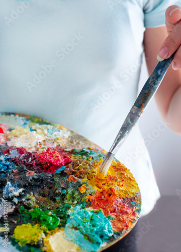 Closeup of girl holding brushes and palette