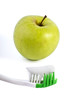 Toothbrush with toothpaste and green apple isolated over white