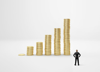 Businessman looking on increasing columns of gold coins