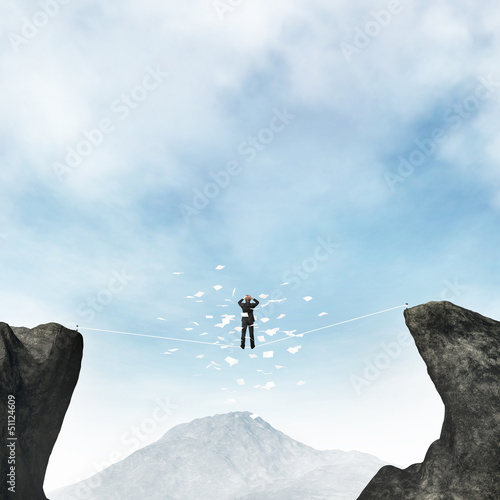 Businessman standing on a rope over the void with flying papers
