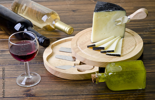 Cheese and wine on wood table.