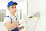 Plasterer with putty knife at wall filling