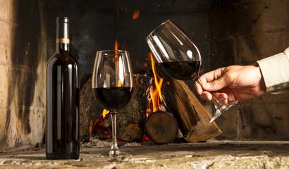 Copa de vino tinto y botella, con fuego de hogar de fondo.